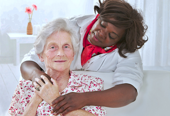 caregiver and elderly woman holding hands