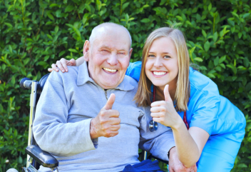elderly man in a wheelchair and caregiver showing their thumbs up