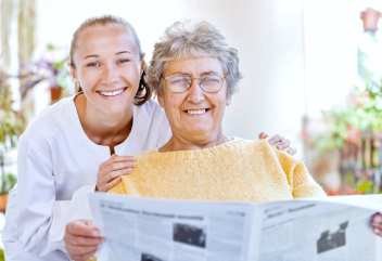 caregiver and elderly woman reading newspaper
