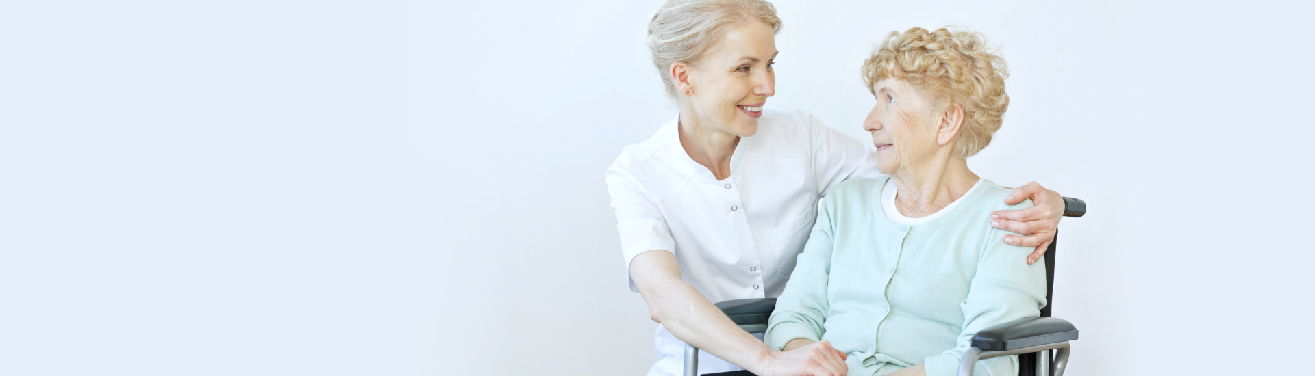 caregiver and elderly woman in a wheelchair smiling