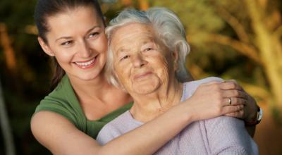 caregiver embracing elderly woman