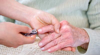 cutting elderly woman's nail