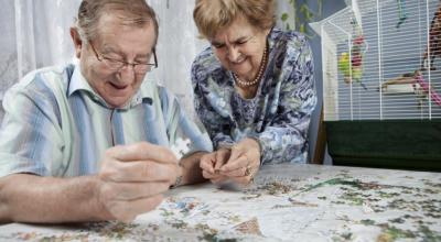 elderly couple playing puzzle